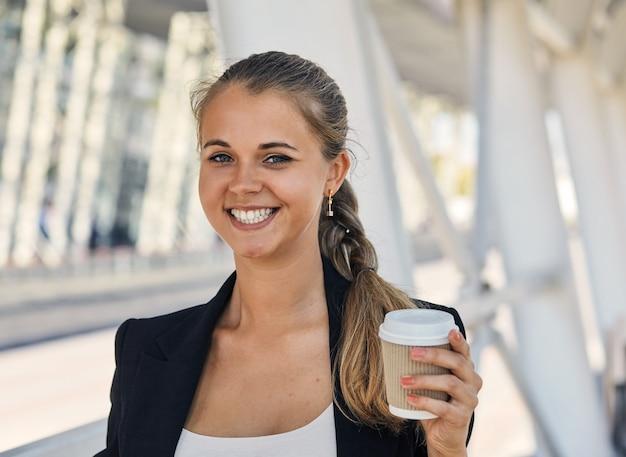 Wesoła modna kobieta trzyma kawę na zewnątrz