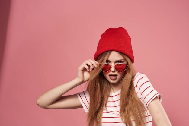 Wesoła modna kobieta w letnim stylu pozowanie w czerwonym kapeluszu