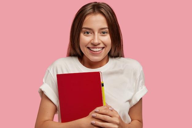Wesoła nastolatka ma zębaty uśmiech, zdrową skórę, długie ciemne włosy, nosi czerwony notes z długopisem