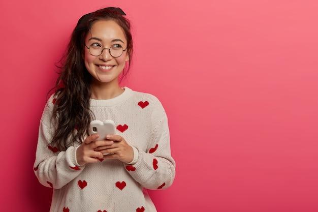Wesoła nastolatka robi posty online za pośrednictwem smartfona, patrzy na bok z rozmarzoną miną, aktualizuje profil osobisty, ma optymistyczny nastrój, nosi przezroczyste okulary, swobodny sweter, stoi w domu