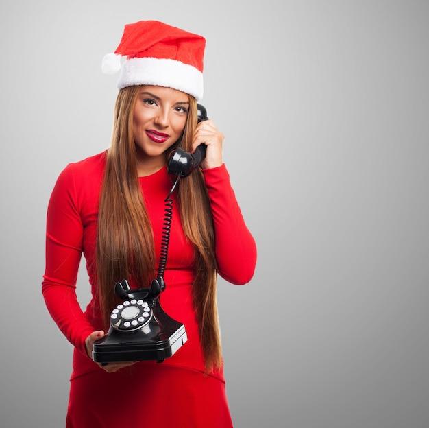 Wesoła nastolatka rozmawia przez telefon z szarym tłem