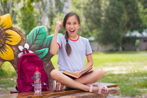 Wesoła nastolatka siedzi na ławce w parku z książką pokazując kciuk do góry powrót do koncepcji szkoły