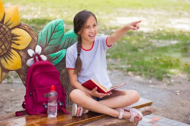 Wesoła nastolatka siedzi na ławce w parku z książką pokazuje palce na bok powrót do szkoły
