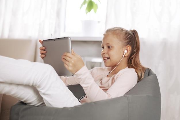 Wesoła nastolatka siedzi w fotelu worek fasoli w białym pokoju, odrabiania lekcji z tabletu