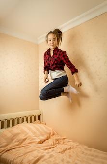 Wesoła nastolatka w koszuli i dżinsach, skacząc na łóżku