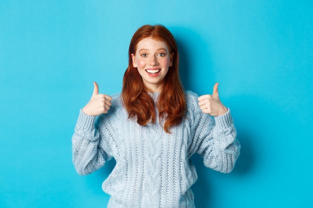 Wesoła nastolatka z rudymi włosami, pokazując kciuki w górę w geście aprobaty, jak i chwały, stojąc na niebieskim tle
