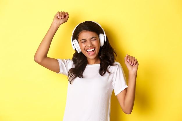 Wesoła nastoletnia afrykańska dziewczyna słucha muzyki w słuchawkach tańczy optymistycznie i uśmiecha się st...
