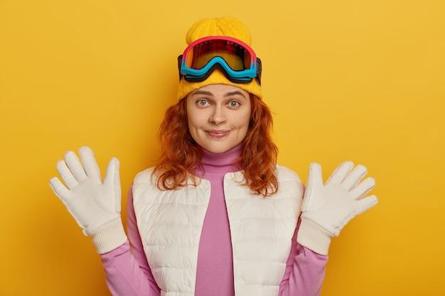 Wesoła naturalna kobieta podnosi ręce w białych rękawiczkach, nosi okulary snowboardowe, cieszy się słonecznym zimowym dniem, radośnie patrzy w kamerę, pozuje na żółtym tle.
