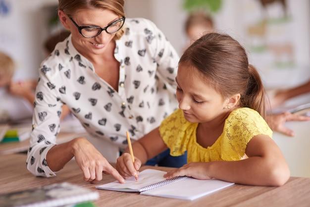 Wesoła nauczycielka pomaga swojemu uczniowi