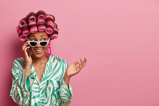 Wesoła, niezdecydowana gospodyni domowa rozmawia przez telefon, słucha plotek i otrzymuje przyjemną ofertę, nosi lokówki, okulary przeciwsłoneczne i szlafrok, patrzy na bok radośnie pozuje na różowej ścianie pustej przestrzeni na tekst