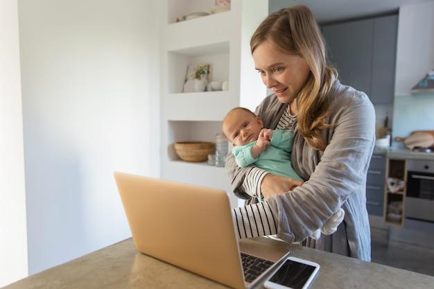 Wesoła nowa mama na biegunach dziecka