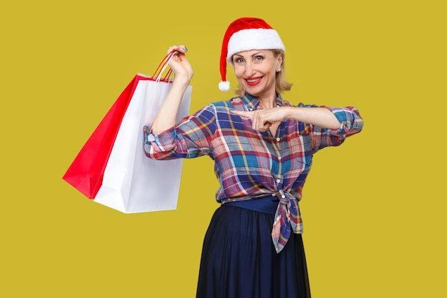 Wesoła nowoczesna kobieta w średnim wieku w czerwonej czapce santa i kraciastej koszuli stojąc i wskazując palcem na torby na zakupy i uśmiech toothy, patrząc na kamery. wewnątrz, strzał studyjny, żółte tło