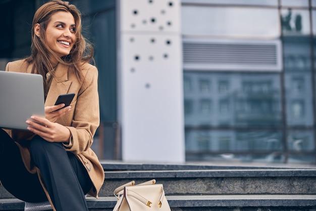 Wesoła nowoczesna młoda kaukaska kobieta z notatnikiem i smartfonem siedząca na schodach