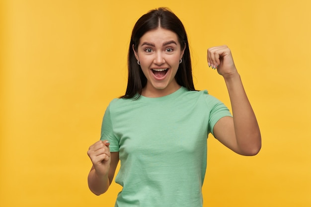 Wesoła, odnosząca sukcesy brunetka, młoda kobieta w miętowej koszulce, krzycząca i świętująca zwycięstwo na białym tle nad żółtą ścianą