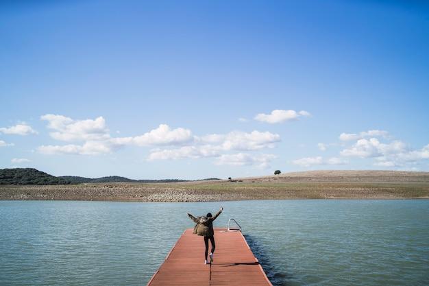Wesoła osoba skacząca na przystani w pobliżu jeziora pod zachmurzonym niebem