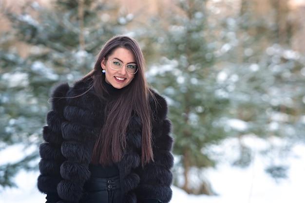 Wesoła pani w okularach i płaszczu pozuje z radością na zewnątrz w zaśnieżonym lesie