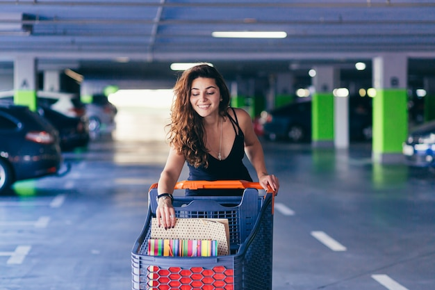 Wesoła pani w stylowej czarnej sukience niosąca kolorowe torby na zakupy na parkingu w pobliżu samochodu.