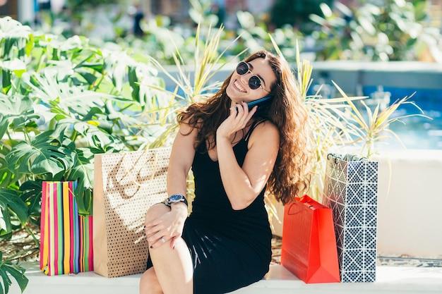 Wesoła pani w stylowej czarnej sukience niosąca kolorowe torby na zakupy podczas spaceru po sklepie