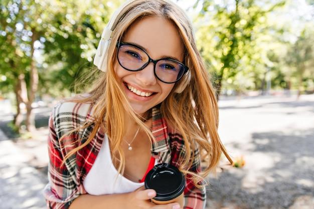 Wesoła panienka w okularach, ciesząc się kawą w parku. odkryty zdjęcie błogiej dziewczyny kaukaskiej zabawy na świeżym powietrzu i słuchania muzyki.