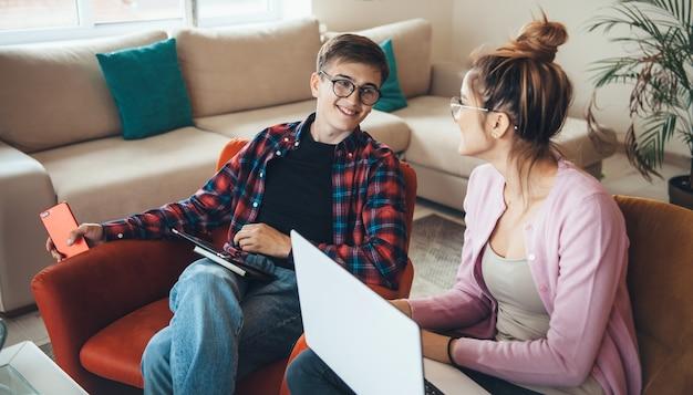 Wesoła para kaukaski w okularach, pracująca w domu