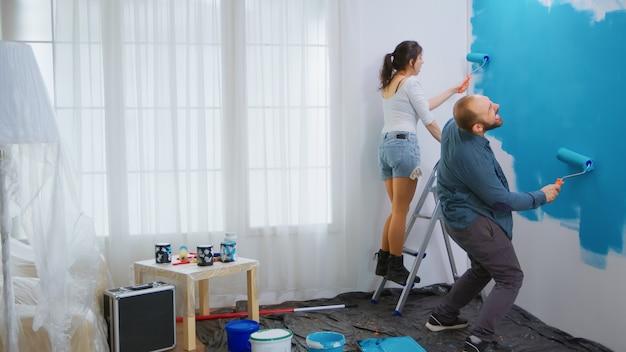 Wesoła para maluje i tańczy podczas remontu salonu. szczęśliwa rodzina. remont mieszkania i budowa domu podczas remontu i modernizacji. naprawa i dekorowanie.