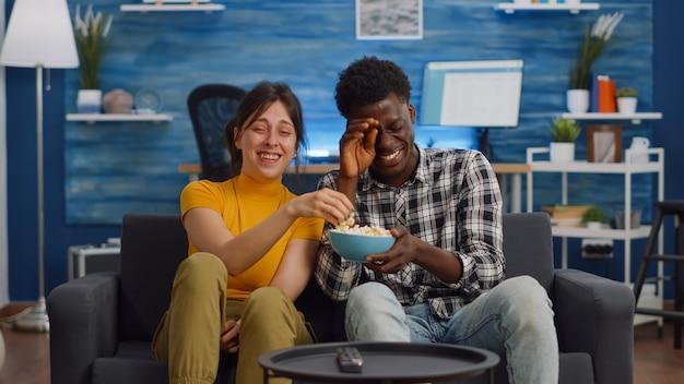 Wesoła para międzyrasowa śmiejąca się z komedii w telewizji