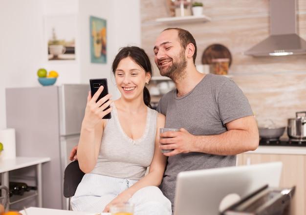 Wesoła para rozmawia z przyjaciółmi na wideorozmowę rano, siedząc na krześle w kuchni. radosny mąż i żona robiący śmieszne miny podczas robienia zdjęć podczas śniadania w kuchni
