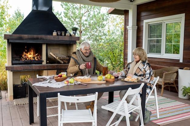 Wesoła para starszych w ciepłych ubraniach na co dzień pijąca herbatę siedząc przy stole, podana z domowym ciastem i świeżymi gruszkami i jabłkami z ogrodu