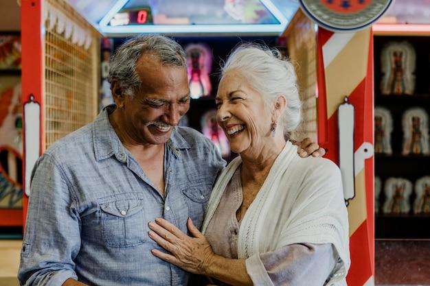 Wesoła para starszych w salonie gier