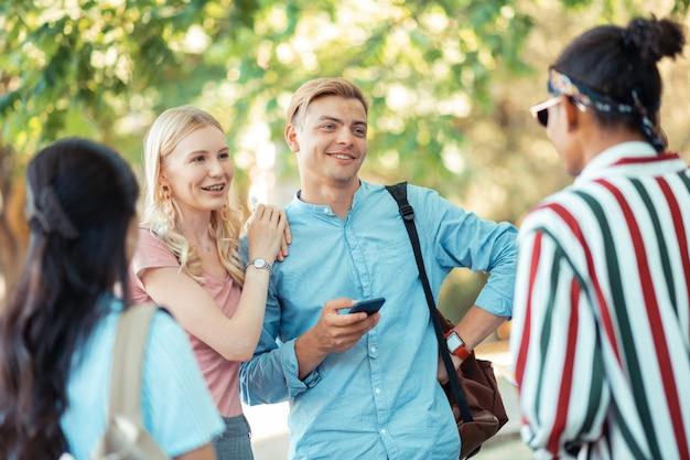 Wesoła para studentów stojących przed uniwersytetem i rozmawiających z przyjaciółmi