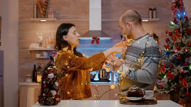 Wesoła para zaplątała się w girlandę świątecznych lampek
