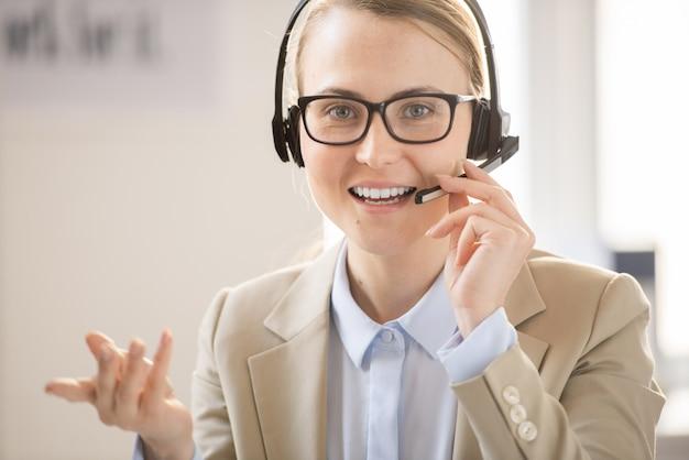 Wesoła, pewna siebie operatorka linii pomocy gestykuluje ręką i reguluje mikrofon podczas rozmowy z klientem przez zestaw słuchawkowy
