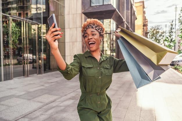 Wesoła piękna afro american kobieta w modnym kombinezonie, patrząc na ekran swojego telefonu komórkowego na zewnątrz
