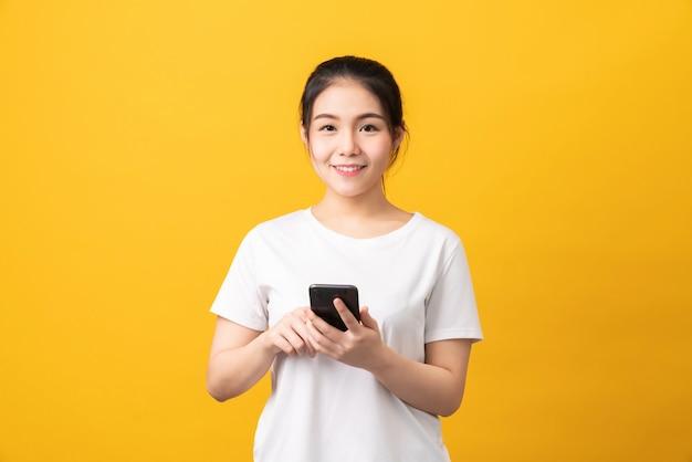 Wesoła piękna azjatycka kobieta trzymając smartfon na jasnożółtym tle.