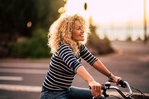 Wesoła piękna blondynka kręcona kaukaska kobieta uśmiecha się i cieszy jazdą na rowerze w czasie wolnym na świeżym powietrzu w mieście - wolni i radośni aktywni ludzie na ulicy bawią się