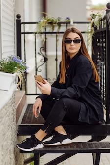 Wesoła piękna brunetka kobieta w dobrym nastroju używa telefonu na zewnątrz