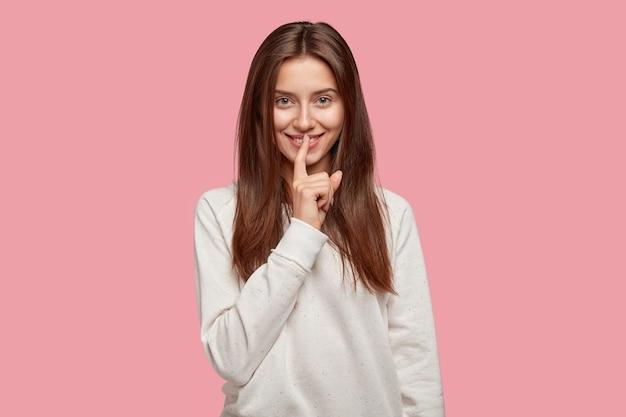 Wesoła piękna brunetka pozuje na różowej ścianie