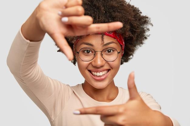Wesoła piękna ciemnoskóra dziewczyna robi ramę obiema rękami, ma zadowolony wyraz twarzy, uśmiecha się szeroko