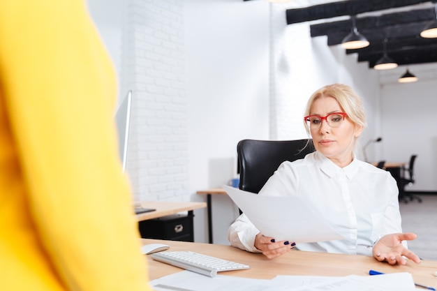 Wesoła piękna dojrzała bizneswoman przeprowadzająca rozmowę kwalifikacyjną z kandydatem na nowe stanowisko w biurze