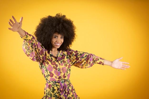 Wesoła piękna i niesamowita pani afro rozkłada ręce w geście uścisków