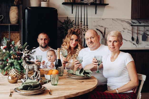 Wesoła piękna kaukaska rodzina z dzieckiem świętuje nowy rok przy drewnianym stole w kuchni.