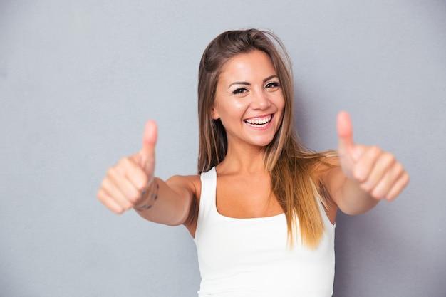 Wesoła piękna kobieta pokazuje kciuki do góry