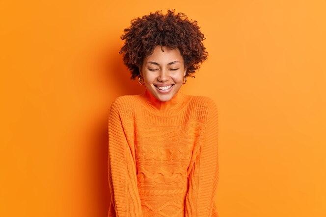 Wesoła piękna kobieta zamyka oczy i uśmiecha się szeroko, nosi sweter z długimi rękawami, pozuje na jaskrawej pomarańczowej ścianie, ma szczęśliwy uśmiech na twarzy
