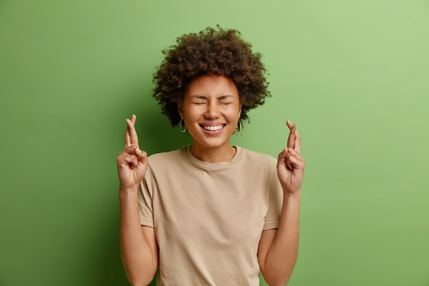 Wesoła, piękna, kręcona, etniczna młoda kobieta krzyżuje palce czeka na ogłoszenie wyników nadzieje marzenia się spełniają uśmiechy szeroko ubrane w casualową koszulkę odizolowaną na zielonej ścianie
