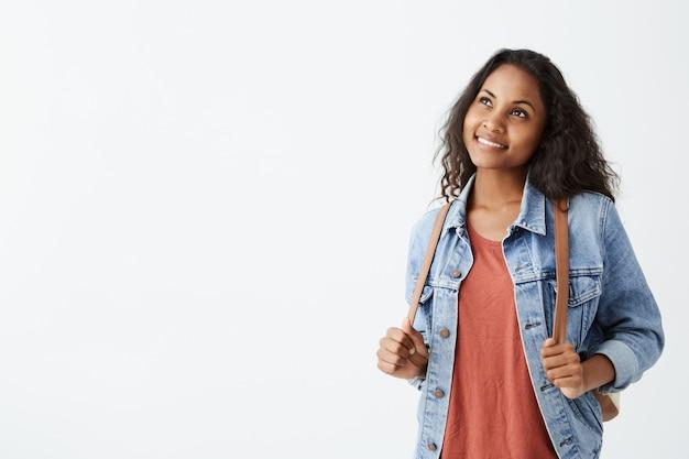 Wesoła piękna młoda afroamerykańska kobieta ubrana w dżinsową kurtkę i czerwoną koszulkę z ciemnymi włosami, uśmiechająca się sennie, myśląc o czymś przyjemnym. ładna dziewczyna ubrana od niechcenia