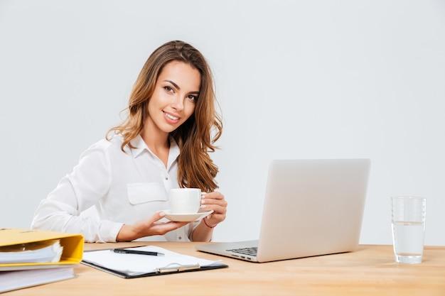Wesoła piękna młoda bizneswoman pije kawę w miejscu pracy na białym tle