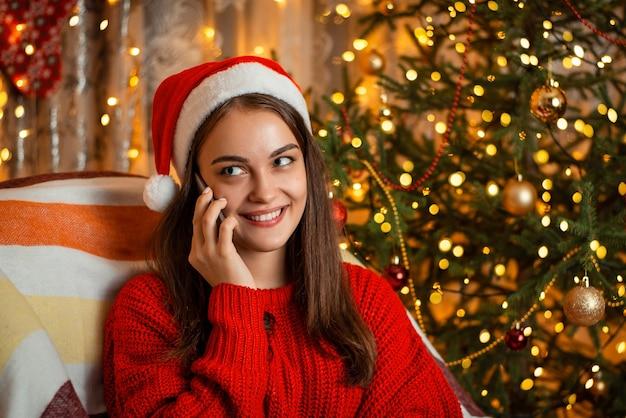 Wesoła piękna młoda kobieta komunikuje się ze swoim najlepszym przyjacielem za pomocą smartfona