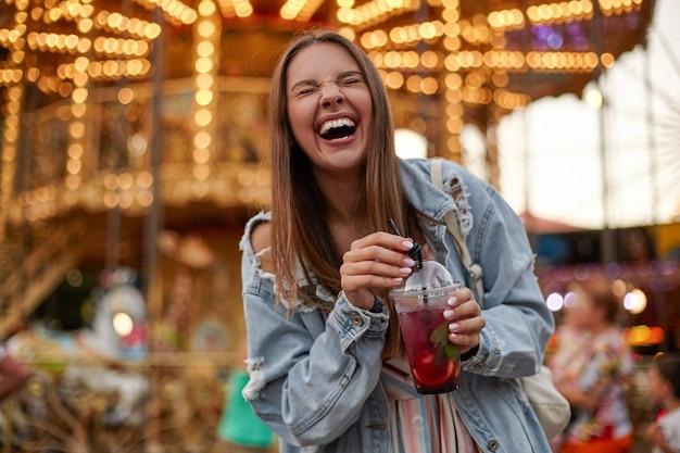 Wesoła piękna młoda kobieta o brązowych włosach w zwykłych ubraniach pije lemoniadę podczas spaceru w parku rozrywki, śmiejąc się głośno z zamkniętymi oczami i marszcząc się