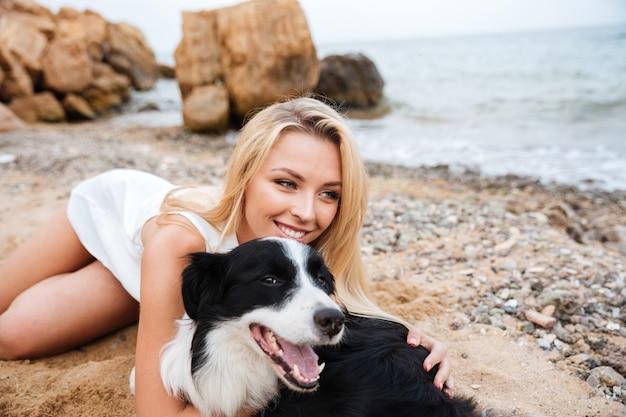 Wesoła piękna młoda kobieta przytulająca psa na plaży
