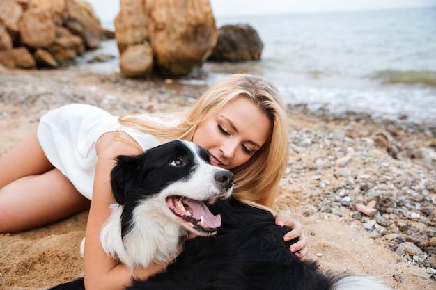 Wesoła Piękna Młoda Kobieta Przytulająca Psa Na Plaży Premium Zdjęcia
